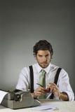 Hübscher Verfasser mit Schreibmaschine Stockfoto