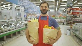 Hübscher Verkäufer mit den Lebensmittelgeschäftpapiertüten, die im Supermarkt stehen, lächelt er an der Kamera stock footage