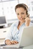 Hübscher Verteiler, der beim Bürolächeln arbeitet lizenzfreies stockfoto