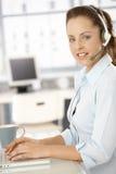 Hübscher Verteiler, der im hellen Bürolächeln arbeitet stockfotos