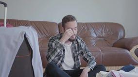 H?bscher verwirrter b?rtiger Mann, der zu Hause auf dem Boden nahe dem Koffer vor ledernem Sofa, viel Kleidung sitzt stock video