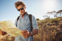 Hübscher Wanderer, der eine Karte verwendet Stockfoto
