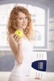 Hübscher weiblicher Holdingapfel und -skala in den Händen Stockfoto