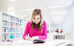 Hübscher, weiblicher Kursteilnehmer mit Laptop und Bücher Stockbild