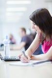 Hübscher weiblicher Kursteilnehmer mit Laptop und Büchern Lizenzfreies Stockbild