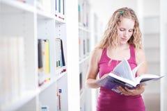 Hübscher weiblicher Student in einer Bibliothek Lizenzfreies Stockfoto