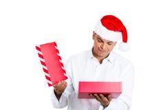 Hübscher Weihnachtsmann nicht sehr glücklich an seinem Geschenk Stockfotografie