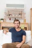 Hübscher youn Mann, der auf einem Sofa sitzt Lizenzfreie Stockfotos