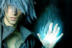 Hübscher Zauberer, der eine blaue Feuerkugel herstellt Stockfoto