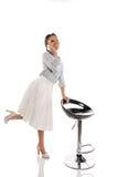 Hübsches Afroamerikanerpin-up-girl, das auf Smartphone beim Lehnen auf Stuhl spricht Stockfotos