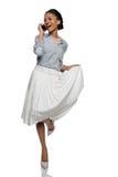 Hübsches Afroamerikanerpin-up-girl, das auf Smartphone spricht Lizenzfreie Stockbilder