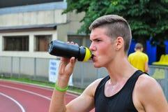 Hübsches althlete Trinkwasser nach laufendem Rennen Lizenzfreies Stockfoto