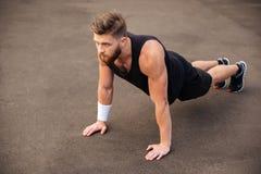 Hübsches Athletentraining des jungen Mannes und Handelnplanke trainieren draußen Stockfotos