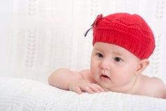 Hübsches Baby im roten Hut Stockfoto