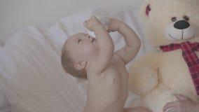 Hübsches Baby trinkt Wasser von der Flasche, die zu Hause auf Bett sitzt Entzückendes kaukasisches Kind zuhause stock footage