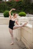 Hübsches Ballettmädchen, das sie Kniesehnen ausdehnt Stockbild