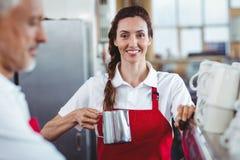 Hübsches barista, das Kamera betrachtet und die Kaffeemaschine verwendet Lizenzfreies Stockbild