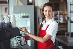 Hübsches barista, das Kamera betrachtet und die Kaffeemaschine verwendet Stockfotografie