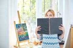 Hübsches blode Mädchen, das auf einem Album und einem Lächeln schaut Kunstkonzept, Stockbilder