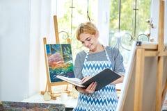 Hübsches blode Mädchen, das auf einem Album und einem Lächeln schaut Kunstkonzept, Lizenzfreies Stockfoto