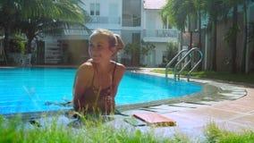 Hübsches blondes Mädchen in den Bikiniresten auf Rand des Poollächelns stock video