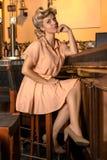 Hübsches blondes Mädchen im Stil der fünfziger Jahre, die das sitzen und das Lehnen auf einem Stangenzähler warten stockbild