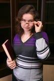 Hübsches Brunetmädchen mit Buch. Stockfotografie