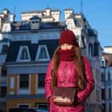 Hübsches Brunette-Mädchen, das den purpurroten den Winter-Mantel, Hut und Schal, gehend durch europäische Straße am Winter trägt, Lizenzfreie Stockfotografie