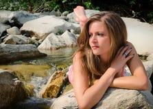 Hübsches Brunettemädchen im Bikini, der auf Felsen legt Stockfoto
