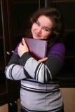 Hübsches Brunettemädchen mit Buch. Lizenzfreies Stockfoto
