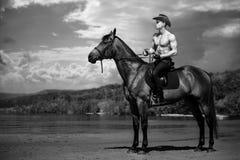 Hübsches Cowboyreiten des Machomannes auf einem Pferd auf dem Hintergrund des Himmels und des Wassers Lizenzfreie Stockfotos