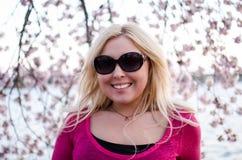 Hübsches Dämmerungssonnenuntergangporträt Blondine, die durch Cherry Blossom-Blumen aufwerfen stockbilder