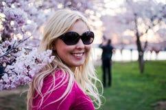 Hübsches Dämmerungssonnenuntergangporträt Blondine, die durch Cherry Blossom-Blumen in DC aufwerfen lizenzfreie stockfotos