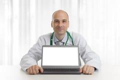 Hübsches doktor, das an einem Schreibtisch mit Laptop sitzt Stockfotografie