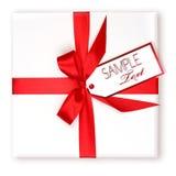 Hübsches eingewickeltes Feiertags-Geschenk mit rotem Farbband und Gi Stockfotografie