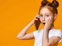 Hübsches emotionales kleines Mädchen, das durch Handy spricht lizenzfreie stockbilder