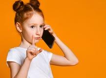 Hübsches emotionales kleines Mädchen, das durch Handy spricht lizenzfreie stockfotos