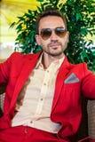 Hübsches erwachsenes Modell, das rote Jacke und moderne Sonnenbrille trägt Stockbild