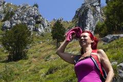 Hübsches Frau Trekkerabwischen geschwitzt von ihrer Stirn Stockbilder