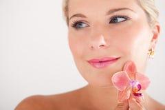Hübsches Frau whith reine gesunde Haut und Orchidee Stockfotos