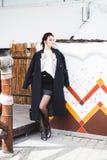 Hübsches Frauenmodell der Mode, das einen dunklen Mantel und eine weiße Strickjacke aufwerfen über ethnischem Hintergrund trägt lizenzfreie stockfotos