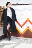 Hübsches Frauenmodell der Mode, das einen dunklen Mantel und eine weiße Strickjacke aufwerfen über ethnischem Hintergrund trägt stockfoto