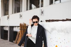 Hübsches Frauenmodell der Mode, das einen dunklen Mantel und eine weiße Strickjacke, in der Sonnenbrille, werfend über weißem Hin lizenzfreie stockbilder