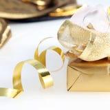 Hübsches Gold eingewickeltes Geschenk und gewirbeltes Band Stockfotos
