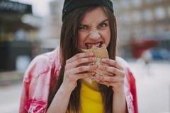 Hübsches Hippie-Mädchen, das hungrig Würstchen isst lizenzfreies stockfoto