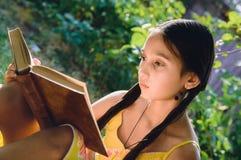 Hübsches jugendlich Mädchen, das ein Buch im Garten liest stockfoto