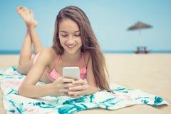 Hübsches Jugendlichmädchen, das ein intelligentes Telefon liegt auf dem Strand mit dem Meer und Horizont im Hintergrund verwendet Stockfotografie