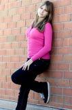 Hübsches Jugendlichmädchen, das nahe bei einer Backsteinmauer steht lizenzfreie stockfotos