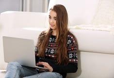 Hübsches Jugendlichmädchen mit dem Laptop, der im Raum sitzt lizenzfreie stockbilder