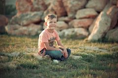 Hübsches Jungenkind, das im Sommer Central Park auf dem grünen frischen Gras trägt stilvolle Kleidungs- und Sonnenbrilleschatten  lizenzfreies stockbild